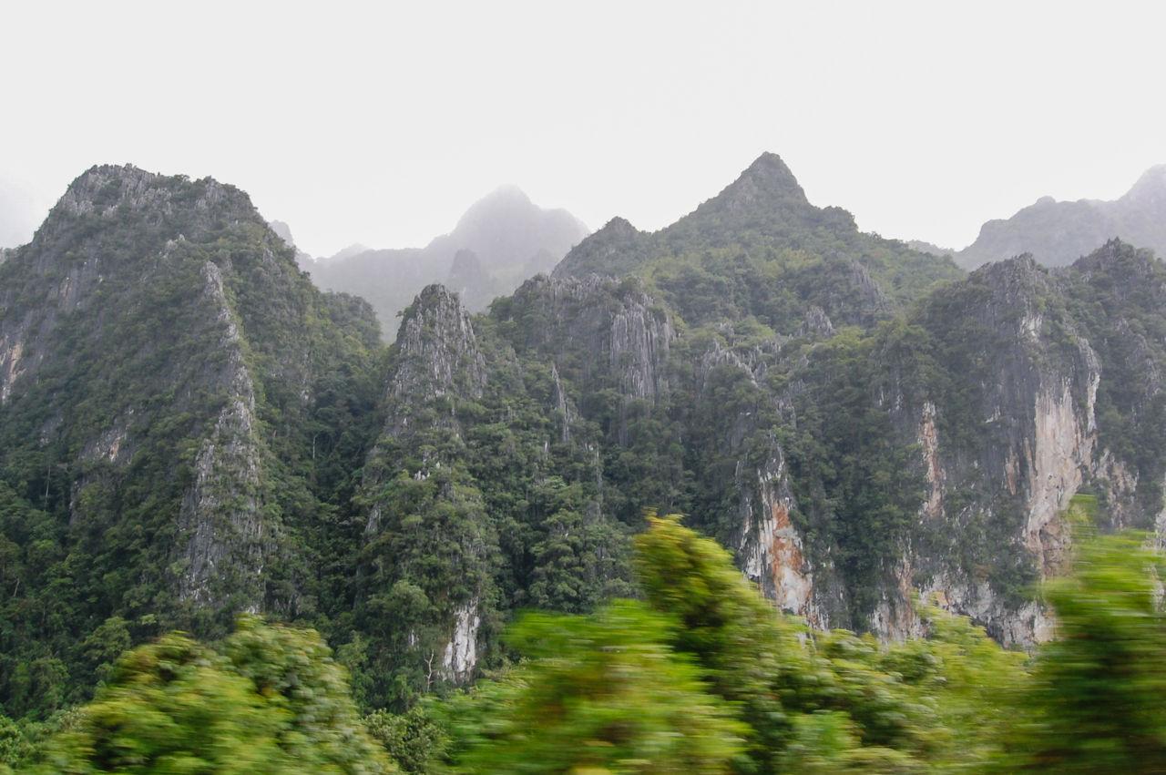 ラオスのバスの車窓に流れる山々の景色